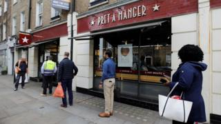 People queue outside a Pret A Manger shop in London