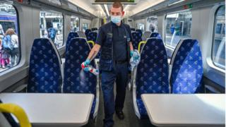 A railway worker cleans a carriage