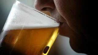 Man drinking pint of lager